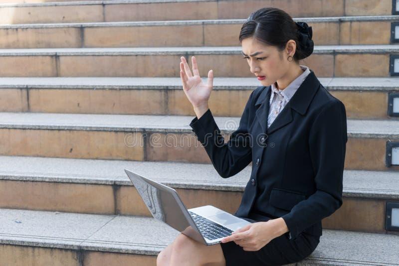 Η τονισμένη επιχειρησιακή γυναίκα κάθεται στη σκάλα και εξέταση το lap-top τονίζει μετά από το επιχειρησιακό λάθος στοκ εικόνα με δικαίωμα ελεύθερης χρήσης