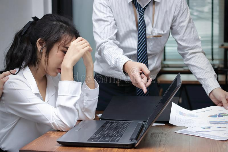Η τονισμένη καταθλιπτική νέα ασιατική επιχειρησιακή γυναίκα κατηγορείται με τον προϊστάμενο στον εργασιακό χώρο του γραφείου στοκ φωτογραφίες με δικαίωμα ελεύθερης χρήσης