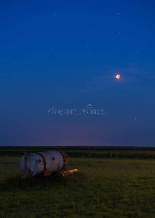 Η τον Ιούλιο του 2018 Bloodmoon έκλειψη που βλέπει σεληνιακή επάνω από ένα λιβάδι σε Schiermonnikoog στοκ εικόνες