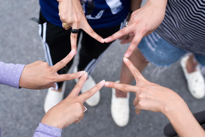 Η τοποθέτηση φίλων γυναικών με τα χέρια και το σημάδι αστεριών στάσης δάχτυλων και η παρουσίαση μαζί, επιτυχής έννοια ομαδικής ερ στοκ φωτογραφία με δικαίωμα ελεύθερης χρήσης