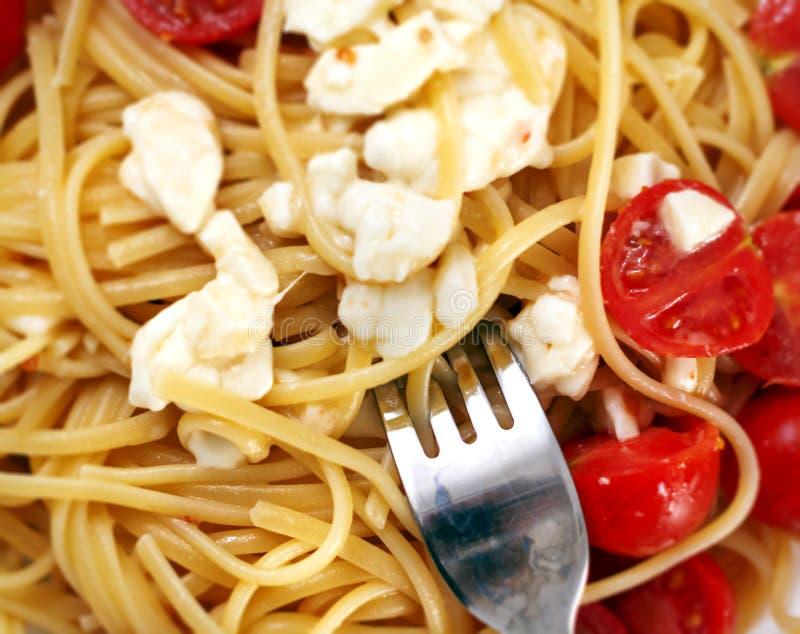 Η τοπ άποψη ενός πιάτου των μακαρονιών καρύκεψε με τις ντομάτες κερασιών και τη φρέσκια μοτσαρέλα με ένα δίκρανο έτοιμο να τους κ στοκ εικόνα