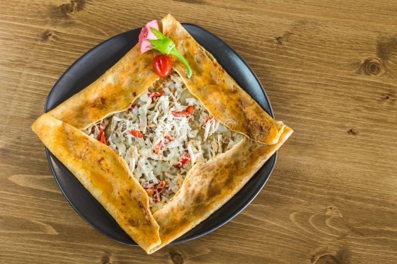 Η τοπ άποψη εύγευστου crepe με το κοτόπουλο που εξυπηρετείται σε ένα γκρίζο πιάτο σε έναν ξύλινο πίνακα στοκ εικόνα με δικαίωμα ελεύθερης χρήσης