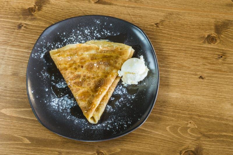Η τοπ άποψη εύγευστου crepe με το μέλι και το παγωτό που εξυπηρετούνται σε ένα γκρίζο πιάτο στοκ εικόνες με δικαίωμα ελεύθερης χρήσης