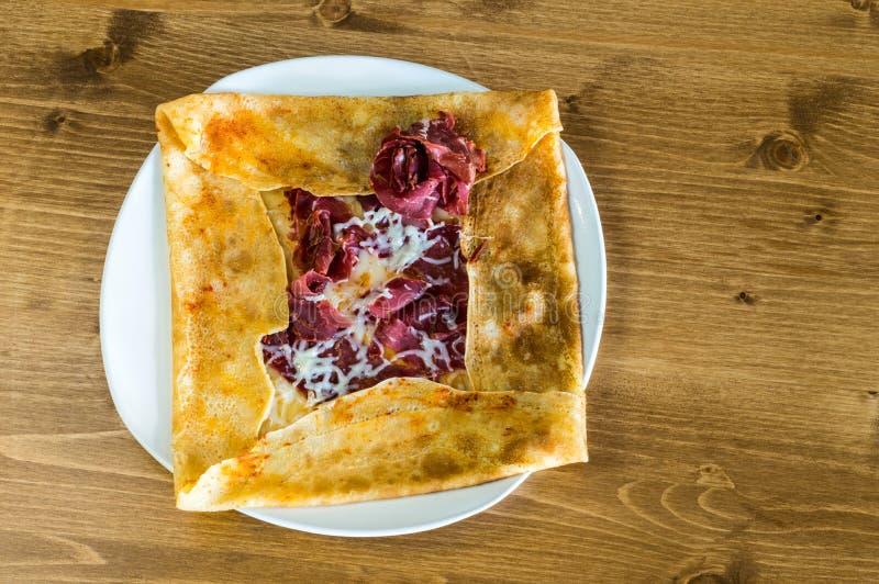 Η τοπ άποψη εύγευστου crepe με το ξηρό pastrami κρέατος που εξυπηρετείται σε ένα άσπρο πιάτο στοκ εικόνες με δικαίωμα ελεύθερης χρήσης