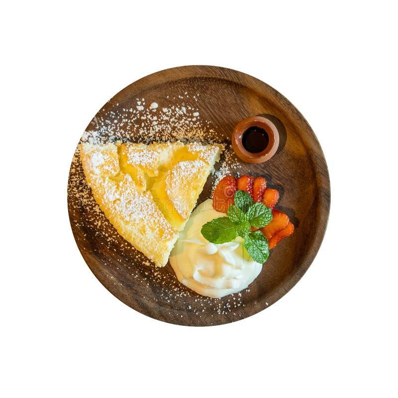 Η τοπ άποψη ιαπωνικό θερμό cheesecake ύφους εξυπηρέτησε με την κτυπημένη κρέμα, τη φρέσκα φράουλα και το σιρόπι μελιού στο ξύλινο στοκ εικόνες