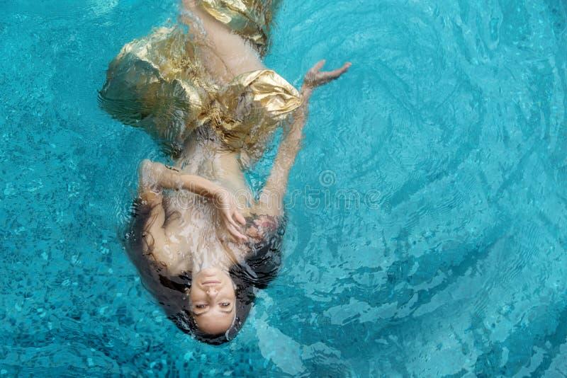 Η τοπ άποψη μιας όμορφης νέας γυναίκας στο χρυσό φόρεμα, που εξισώνει το φόρεμα, πετσέτα επιπλέει weightlessly κομψά να κολυμπήσε στοκ φωτογραφία