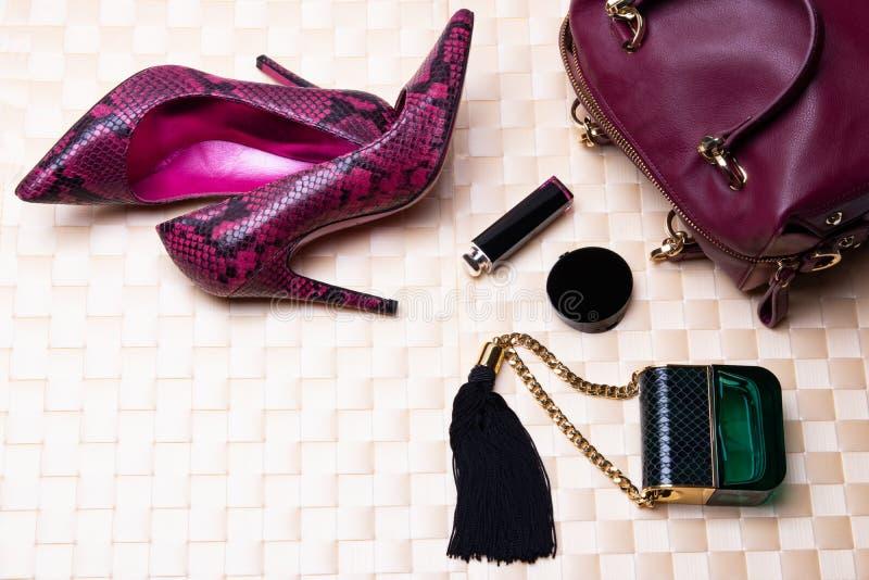 Η τοπ άποψη στο επίπεδο βάζει τα μοντέρνα υψηλά τακούνια, την τσάντα δέρματος, το άρωμα και τα καλλυντικά σε ένα φωτεινό επιτραπέ στοκ φωτογραφίες