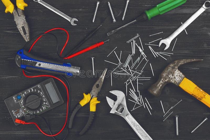 Η τοπ άποψη σχετικά με τα λειτουργώντας εργαλεία χεριών, γαλλικό κλειδί, κατσαβίδι, πένσες, σφυρί, διευθετήσιμο κλειδί, μαχαίρι γ στοκ εικόνες