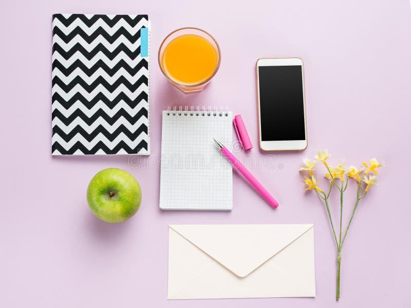 Η τοπ άποψη σχετικά με το θηλυκό γραφείο Το τηλέφωνο και τα γαλλικά macarons στο καθιερώνον τη μόδα ρόδινο γραφείο στοκ φωτογραφία με δικαίωμα ελεύθερης χρήσης
