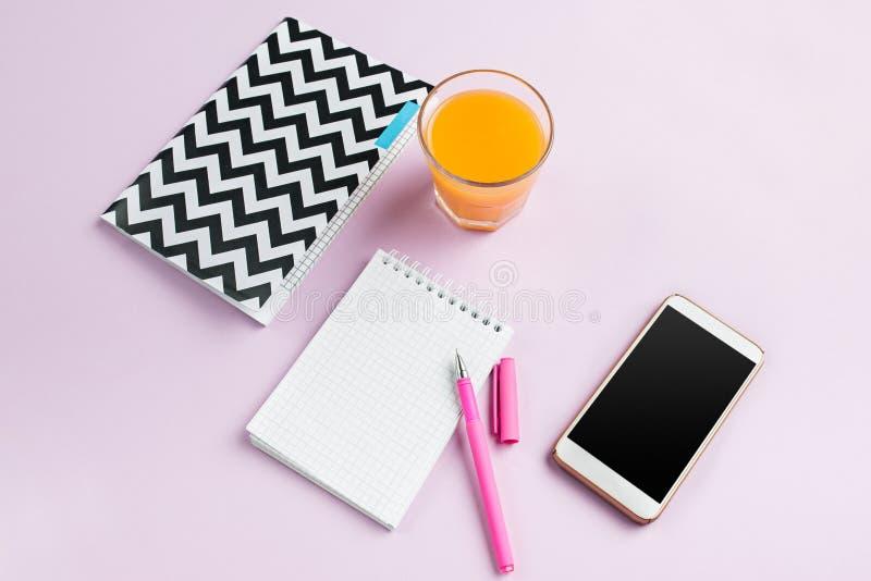 Η τοπ άποψη σχετικά με το θηλυκό γραφείο Το τηλέφωνο και τα γαλλικά macarons στο καθιερώνον τη μόδα ρόδινο γραφείο στοκ εικόνες με δικαίωμα ελεύθερης χρήσης