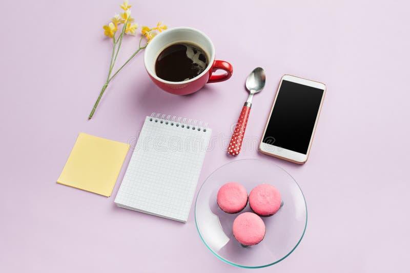 Η τοπ άποψη σχετικά με το θηλυκό γραφείο Το τηλέφωνο και τα γαλλικά macarons στο καθιερώνον τη μόδα ρόδινο γραφείο στοκ φωτογραφία