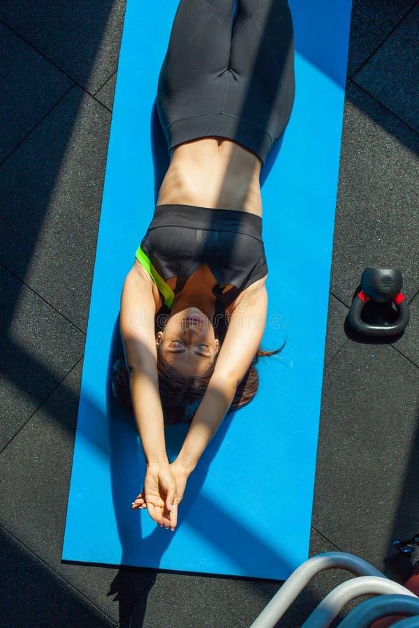 Η τοπ άποψη της γυναίκας στον αθλητισμό ντύνει να βρεθεί στο χαλί κοντά στο βάρος που κάνει την τεντώνοντας άσκηση Γυναίκα ικανότ στοκ εικόνα