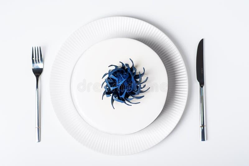 Η τοπ άποψη του γαμήλιου σύγχρονου καθιερώνοντος τη μόδα άσπρου κέικ στο πιάτο απομόνωσε το υπόβαθρο με dinnerware διακοσμημένη τ στοκ φωτογραφία
