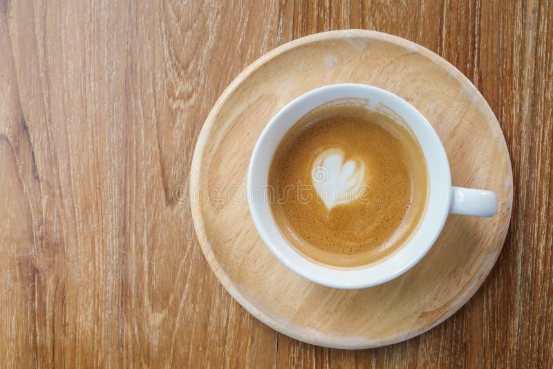Η τοπ άποψη του καυτού καφέ latte κοιλαίνει με το μίνι διαμορφωμένο καρδιά FOA γάλακτος στοκ φωτογραφία