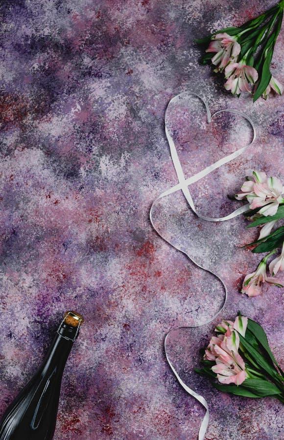 η τοπ άποψη του μπουκαλιού, των λουλουδιών και της καρδιάς σαμπάνιας διαμόρφωσε την κορδέλλα πορφυρό tabletop, βαλεντίνοι στοκ φωτογραφία με δικαίωμα ελεύθερης χρήσης