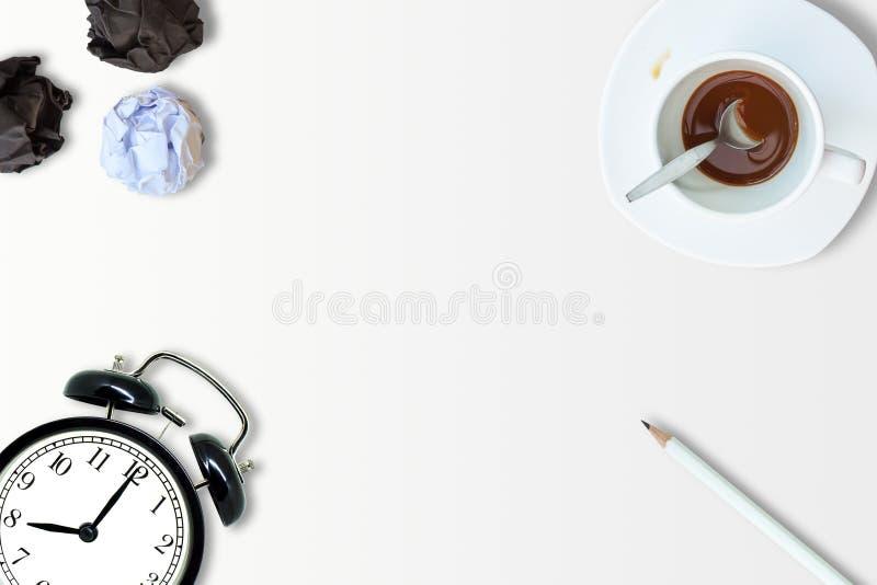 Η τοπ άποψη του φλυτζανιού καφέ, το άσπρο μολύβι, το αναδρομικό ξυπνητήρι και η άσπρη τσαλακωμένη σφαίρα εγγράφου τοποθετούν στο  στοκ εικόνα με δικαίωμα ελεύθερης χρήσης