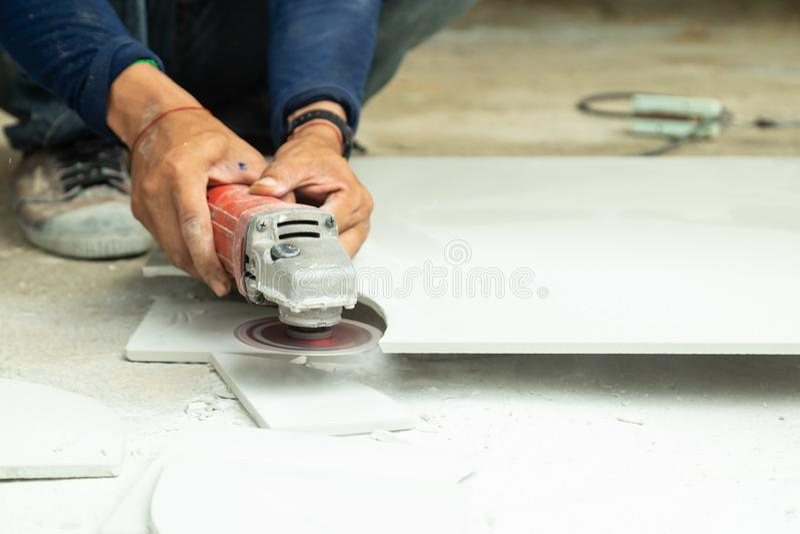 Η τοπ άποψη των εργαζομένων έκοψε τα κεραμίδια στη μορφή με τον ηλεκτρικό κόπτη κεραμιδιών με ή το μύλο γωνίας για να στρώσει το  στοκ φωτογραφίες