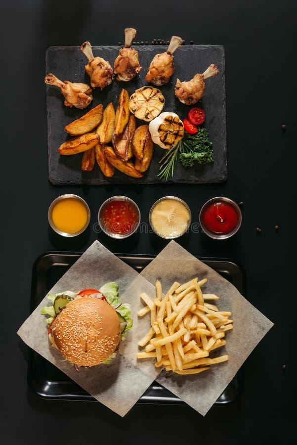 η τοπ άποψη των τηγανιτών πατατών με εύγευστο burger στο δίσκο, τις ανάμεικτους σάλτσες και τον πίνακα πλακών με τις ψημένες πατά στοκ φωτογραφίες με δικαίωμα ελεύθερης χρήσης
