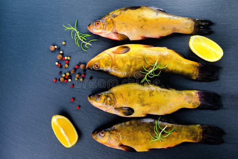 Η τοπ άποψη φρέσκα tench αλιεύει με τα αρωματικά χορτάρια, τα καρυκεύματα και τα λαχανικά στο υπόβαθρο πλακών, στοκ φωτογραφίες με δικαίωμα ελεύθερης χρήσης