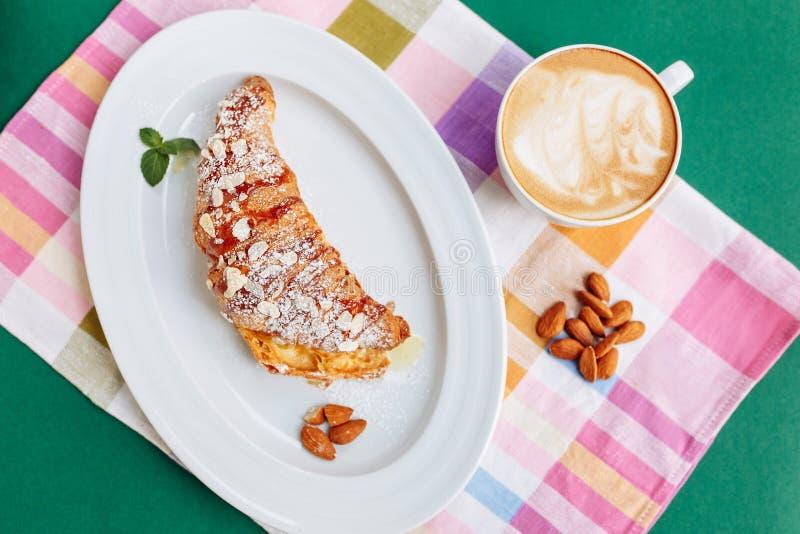 Η τοπ άποψη φρέσκου ψημένου croissant που διακοσμείται με το τεμαχισμένο ψίχουλο αμυγδάλων, η μαρμελάδα και η ζάχαρη κονιοποιούν  στοκ φωτογραφίες με δικαίωμα ελεύθερης χρήσης