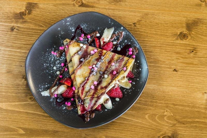 Η τοπ άποψη crepe με την κρέμα σοκολάτας, τα τσιπ σοκολάτας, την μπανάνα και τη φράουλα που εξυπηρετούνται στο γκρίζο πιάτο στοκ φωτογραφίες