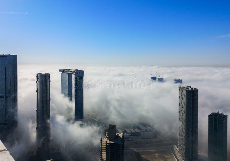 Η τοπ εναέρια άποψη που πυροβολείται των ουρανοξυστών στην πόλη με την ομίχλη καλύπτει τη διάβαση από - πύργοι ήλιων και ουρανού  στοκ φωτογραφία με δικαίωμα ελεύθερης χρήσης