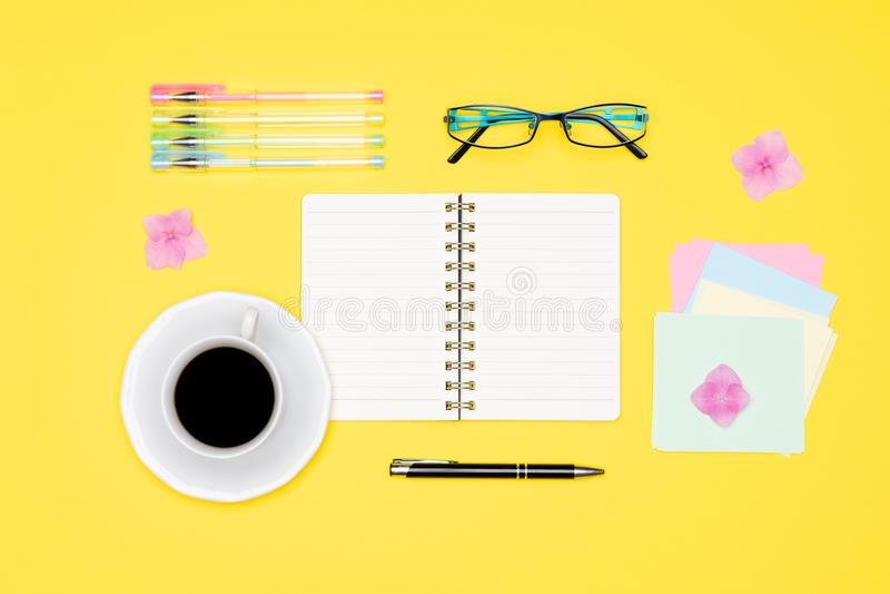 Η τοπ φωτογραφία άποψης του γραφείου γραφείων με το κενά πλαστά επάνω ανοικτά σημειωματάριο, τη μάνδρα, τα γυαλιά και το φλυτζάνι στοκ φωτογραφία με δικαίωμα ελεύθερης χρήσης