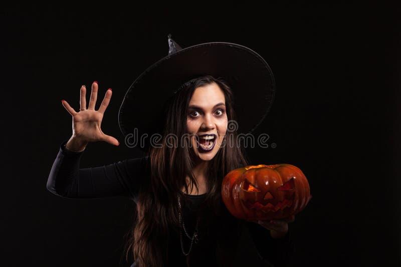 Η τρομακτική γυναίκα έντυσε όπως μια μάγισσα με ένα μεγάλο καπέλο για αποκριές που κρατούν μια κολοκύθα στοκ εικόνες