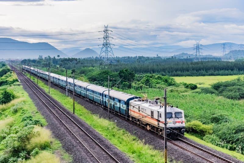Η τρομερή στενή μπροστινή άποψη μηχανών του ινδικού σιδηροδρόμου που τρέχει στη διαδρομή πηγαίνει στον ορίζοντα στο πράσινο τοπίο στοκ φωτογραφία