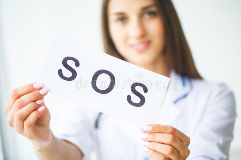 η υγεία προσοχής όπλων απομόνωσε τις καθυστερήσεις Γιατρός που κρατά μια κάρτα με το SOS συμβόλων, ιατρικός συμπυκνωμένος στοκ φωτογραφίες
