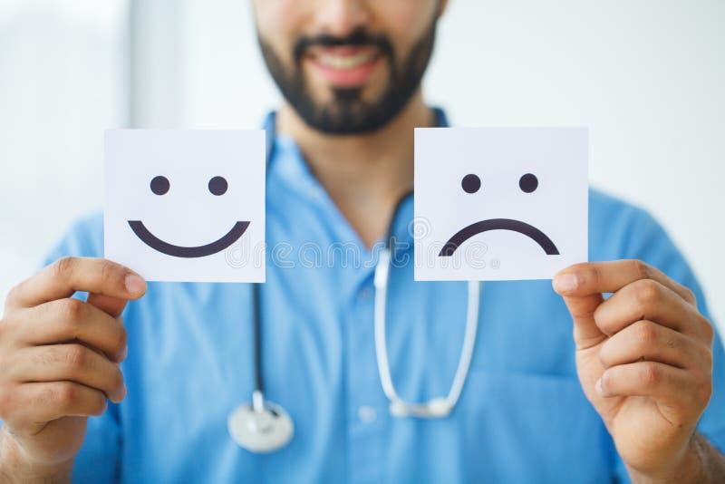 η υγεία προσοχής όπλων απομόνωσε τις καθυστερήσεις Γιατρός που κρατά τις κάρτες με τη διασκέδαση συμβόλων και λυπημένο Smil στοκ εικόνες με δικαίωμα ελεύθερης χρήσης