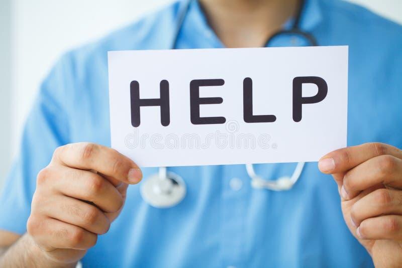 η υγεία προσοχής όπλων απομόνωσε τις καθυστερήσεις Γιατρός που κρατά μια κάρτα με τη ΒΟΗΘΕΙΑ συμβόλων, ιατρικό Con στοκ φωτογραφία