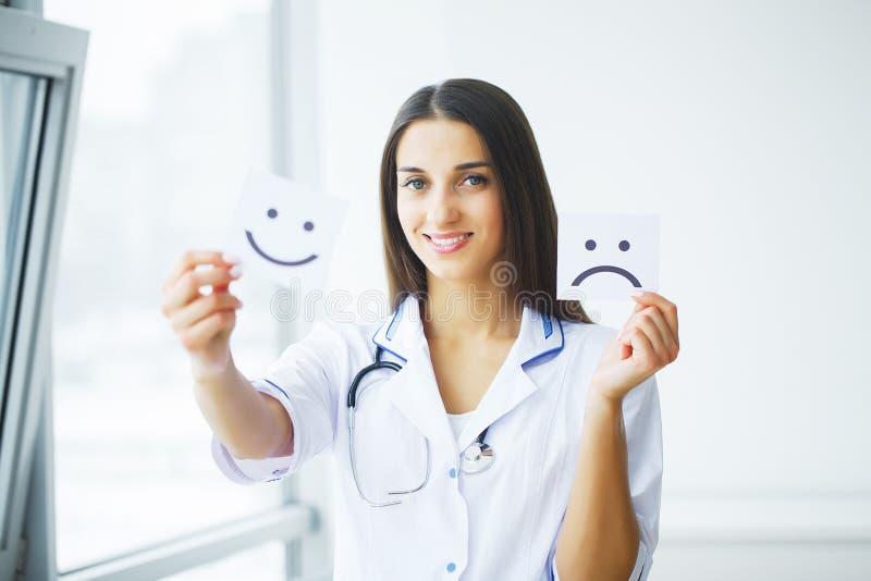 η υγεία προσοχής όπλων απομόνωσε τις καθυστερήσεις Γιατρός που κρατά τις κάρτες με τη διασκέδαση συμβόλων και λυπημένο Smil στοκ φωτογραφίες με δικαίωμα ελεύθερης χρήσης