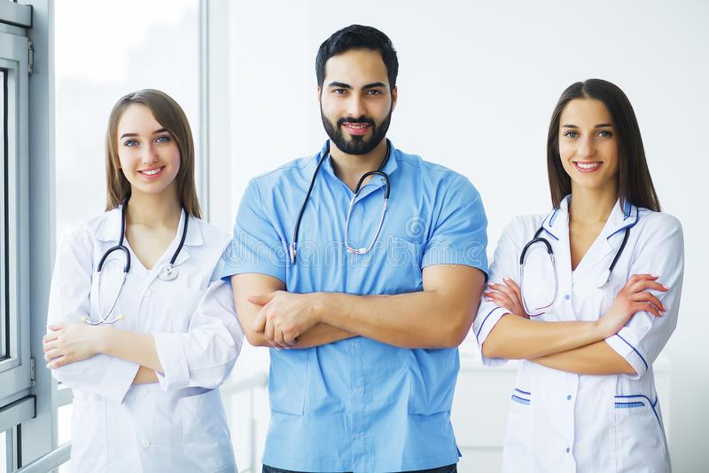 η υγεία προσοχής όπλων απομόνωσε τις καθυστερήσεις Οι ελκυστικοί γιατροί με το ιατρικό στηθοσκόπιο εργάζονται στοκ εικόνα με δικαίωμα ελεύθερης χρήσης
