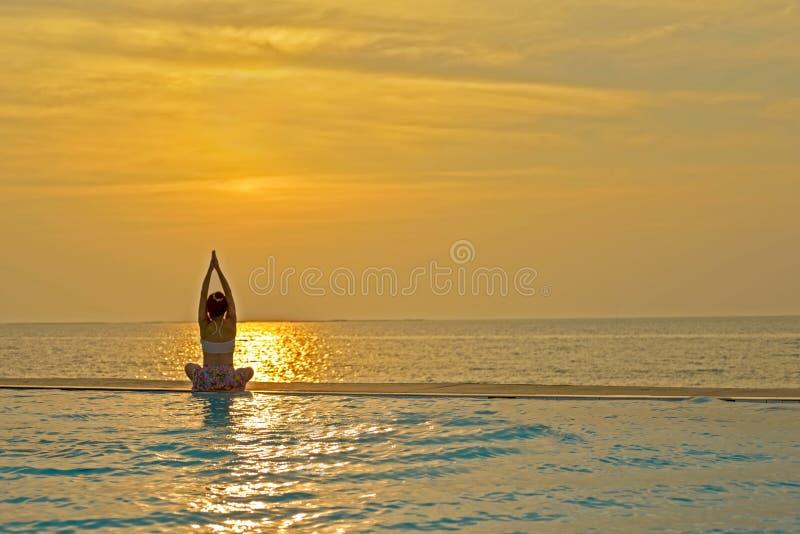Η υγιής γιόγκα άσκησης γυναικών τρόπου ζωής σκιαγραφιών και άσκηση χαλαρώνει το ζωτικής σημασίας meditate στην πισίνα και την παρ στοκ φωτογραφία με δικαίωμα ελεύθερης χρήσης