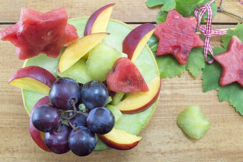 Η υγιής μοναδική σαλάτα φρούτων εξυπηρέτησε σε ένα φρέσκο πεπόνι σε ένα ξύλινο τ στοκ φωτογραφία με δικαίωμα ελεύθερης χρήσης