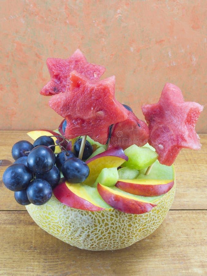 Η υγιής μοναδική σαλάτα φρούτων εξυπηρέτησε σε ένα φρέσκο πεπόνι σε ένα ξύλινο τ στοκ εικόνες