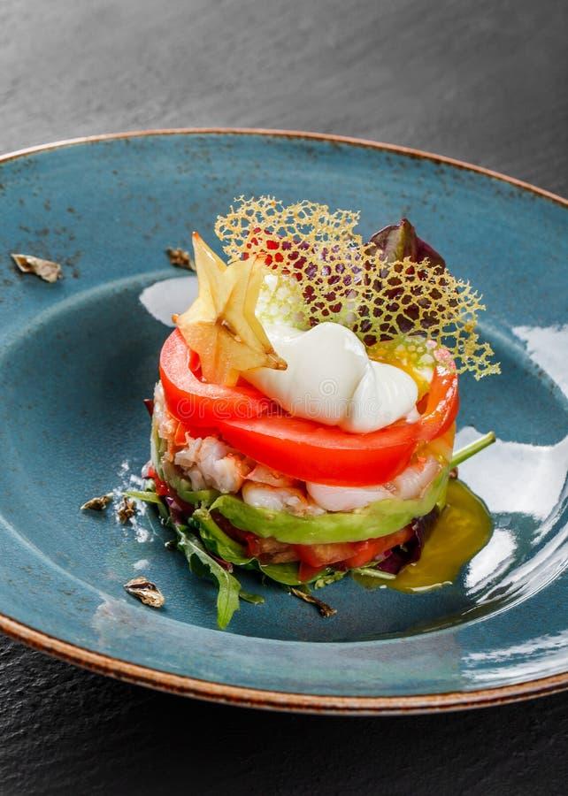 Η υγιής φρέσκια σαλάτα με το αβοκάντο, γαρίδες τιγρών, κάπαρες, ντομάτα, κυνήγησε λαθραία αυγό στο πιάτο πέρα από το σκοτεινό πίν στοκ εικόνες