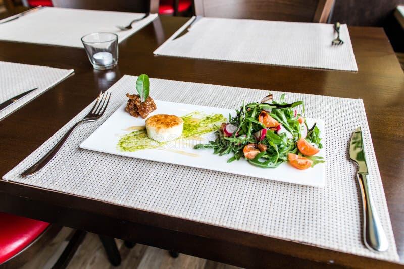 Η υγιής φυτική θερινή σαλάτα, τα φρέσκα λαχανικά και ο επίδεσμος με το ψημένο στη σχάρα τυρί flambe τακτοποίησαν στον πίνακα γευμ στοκ φωτογραφία με δικαίωμα ελεύθερης χρήσης