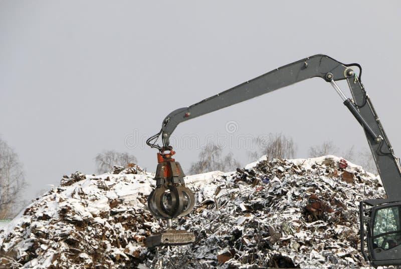Η υδραυλική αρπαγή καθαρίζει και tampens τα συντρίμμια μετάλλων Ο εκσκαφέας ανυψώνει και ρίχνει το φορτίο με ένα πνευματικό πόδι  στοκ φωτογραφία με δικαίωμα ελεύθερης χρήσης