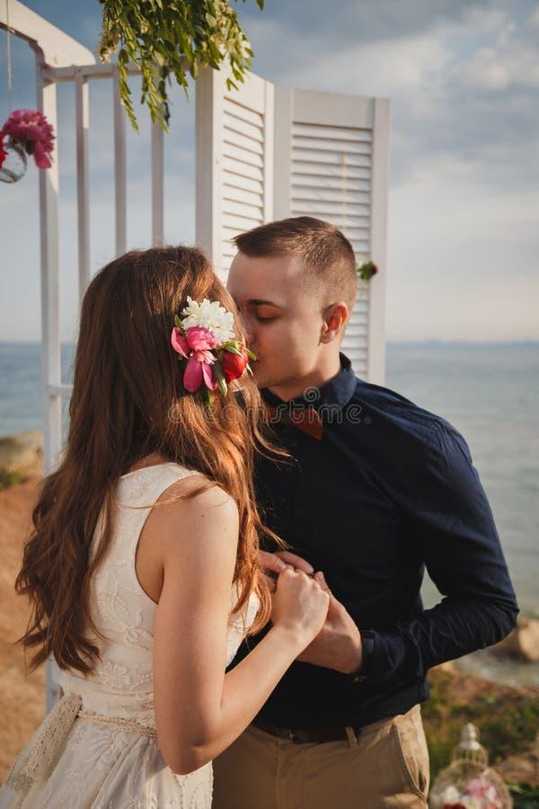 Η υπαίθρια γαμήλια τελετή παραλιών, ο μοντέρνοι ευτυχείς χαμογελώντας νεόνυμφος και η νύφη στέκονται κοντά στη γαμήλια αψίδα στην στοκ φωτογραφία