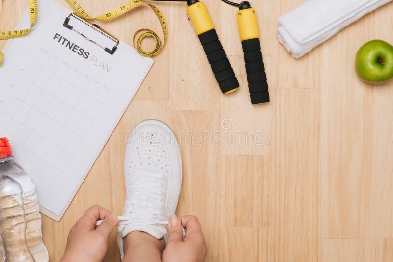 Η υπερυψωμένη άποψη της γυναίκας δίνει τα δένοντας παπούτσια με τους αθλητικούς εξοπλισμούς ο στοκ εικόνες