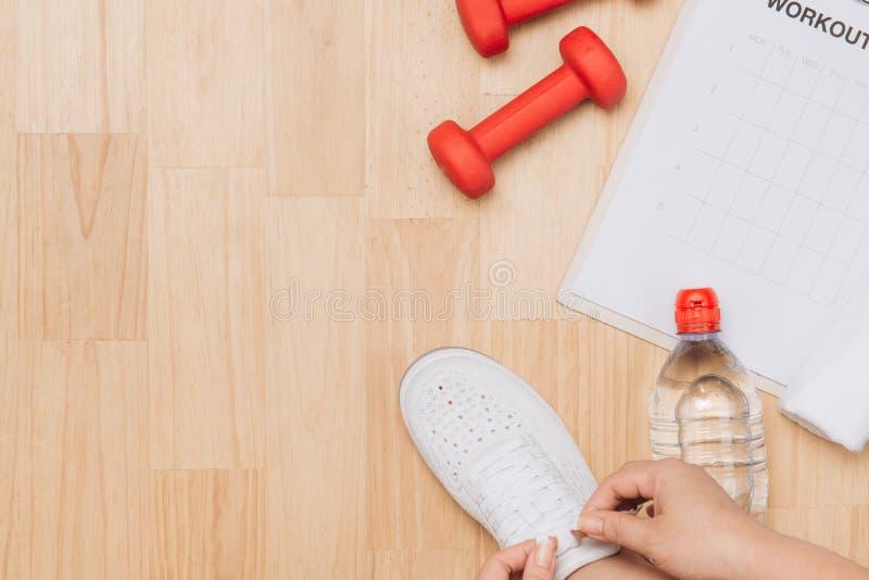 Η υπερυψωμένη άποψη της γυναίκας δίνει τα δένοντας παπούτσια με τους αθλητικούς εξοπλισμούς στο ξύλινο υπόβαθρο στοκ φωτογραφίες με δικαίωμα ελεύθερης χρήσης