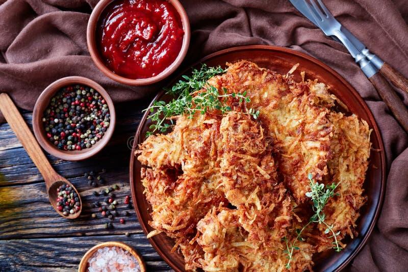 Η υπερυψωμένη άποψη της ξυμένης πατάτας πασπάλισε τις μπριζόλες χοιρινού κρέατος σε ένα πιάτο αργίλου σε έναν αγροτικό ξύλινο πίν στοκ φωτογραφία με δικαίωμα ελεύθερης χρήσης