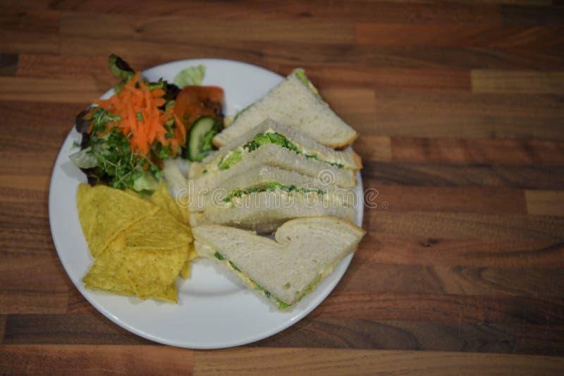 Η υπερυψωμένη άποψη της φωτογραφίας τροφίμων με ένα σπιτικό μεσημεριανό γεύμα των σάντουιτς τυριών και κρεμμυδιών και της δευτερε στοκ εικόνα με δικαίωμα ελεύθερης χρήσης