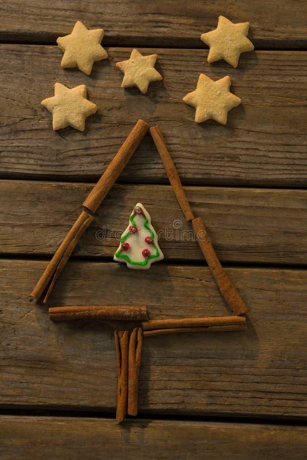 Η υπερυψωμένη άποψη των μπισκότων μορφής αστεριών από το χριστουγεννιάτικο δέντρο έκανε με το ραβδί κανέλας στοκ εικόνες