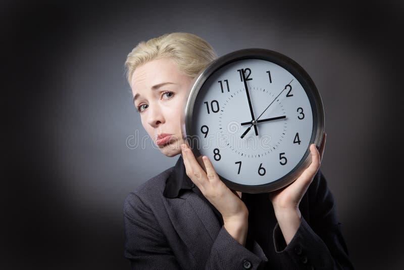 Η δυστυχισμένη γυναίκα κρατά το ρολόι στοκ εικόνες με δικαίωμα ελεύθερης χρήσης