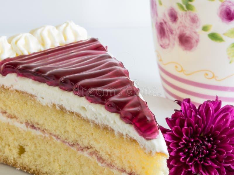 Η φέτα του κέικ βακκινίων και η βιολέτα ανθίζουν, ένα φλυτζάνι του τσαγιού, στη μαλακή εστίαση στοκ φωτογραφίες