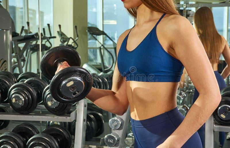 Η φίλαθλη γυναίκα στηρίζεται τα όπλα και το στήθος μυών στον προσομοιωτή στοκ φωτογραφία