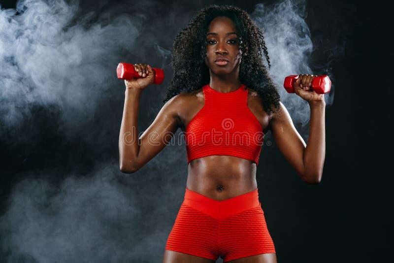 Η φίλαθλη κατάλληλη μαύρη γυναίκα δερμάτων κόκκινο sportswear, αθλητής με τους αλτήρες κάνει την ικανότητα ασκώντας στο σκοτεινό  στοκ φωτογραφία με δικαίωμα ελεύθερης χρήσης